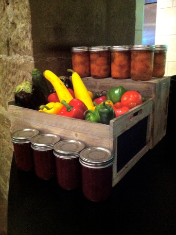 A display of fresh vegetables and homemade preserves.